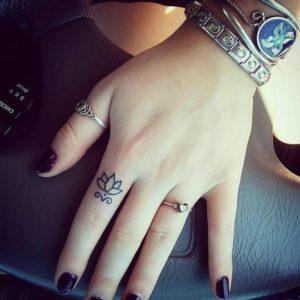 tatuaggio piccolo fiore di loto donna dito mano significato